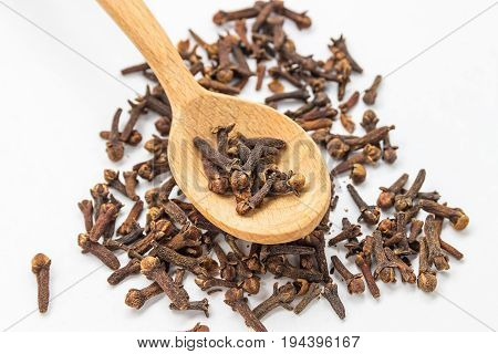 Clove spice. Carnation seasoning. A pile of carnations isolated on a white background in a wooden spoon. Natural spices