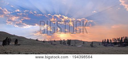 Sunbeams and sunrays through sunset clouds in the Hayden Valley in Yellowstone National Park in Wyoming United States