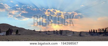 Sunbeams and sunrays through sunset clouds in the Hayden Valley in Yellowstone National Park in Wyoming US