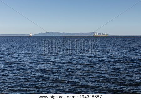 Lake Superior At Thunder Bay with a lighthouse and a ship.