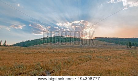 Sunbeams and sunrays through sunset clouds in the Hayden Valley in Yellowstone National Park in Wyoming USA