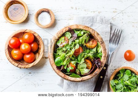 Vegetarian salad with lettuce and tomatoes in olive wooden bowl on wihte background