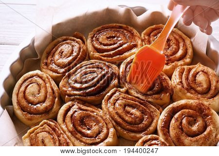 Woman spreading sauce over raw cinnamon rolls with brush in baking pan
