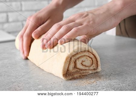 Woman preparing cinnamon roll in kitchen