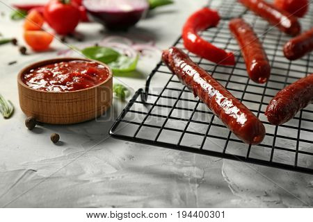 Composition with yummy sausages with sauce on cooling grid, closeup