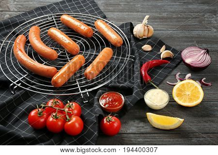 Composition with yummy sausages on cooling grid with vegetables and sauce on wooden table