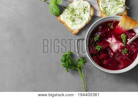 Delicious beet soup with sour cream and parsley on kitchen table