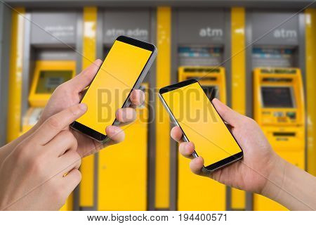 human hand hold and touch blank screen cell phone on blurry automatic transfer machine concept transfer money.