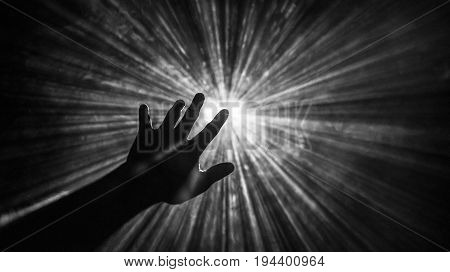 Hand reaches out to touch the light with left index finger