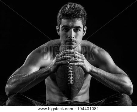 Football player portrait holding american football staring. Male model in his 20s.