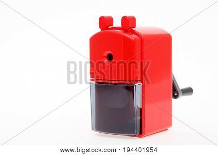 Red plastic pencil sharpener on white background