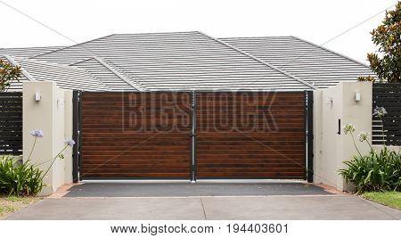 Wooden driveway entrance gates set in brick fence