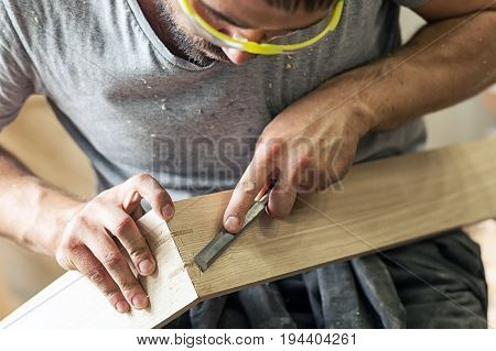 A young brunette man builder wearing green protective goggles a gray T-shirt and a beard treating a wooden product with a chisel in the workshop close-up