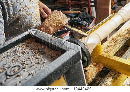 A young male construction worker carpenter processes a wood d on a lathe in the workshop close-up on his hands and around a lot of wooden sawdust in the background a wooden poster