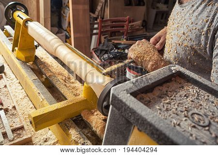 A close-up of how a man makes a wooden product on a lathe in a workshop on his hands and around a lot of wooden sawdust