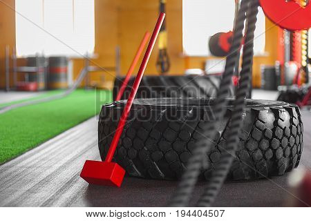 Sports equipment in the gym. Hammer ropes weight and tire