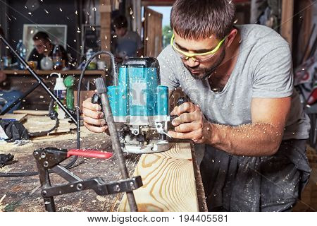 A young man with a beard  by profession the carpenter holds a green milling machine and puts a wooden board in the background there are many wooden boards and equipment