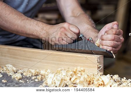 Close-up as a young man holds a black jack plane in his hands and processes a wooden block near a lot of wooden sawdust