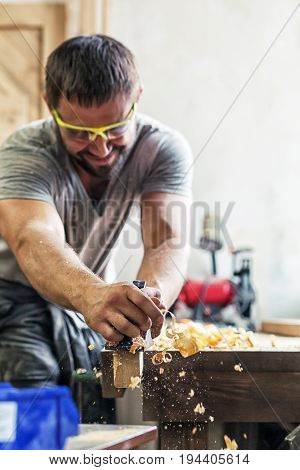A young man with dark hair and wearing goggles is holding a black plane in his hands and is processing a wooden board in his hand flying wood sawdust in the workshop