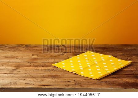 Empty wooden table with tablecloth over yellow background. Autumn season concept