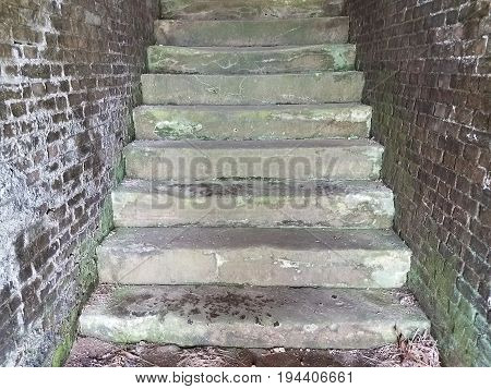 very old stairs and red brick wall with sediment