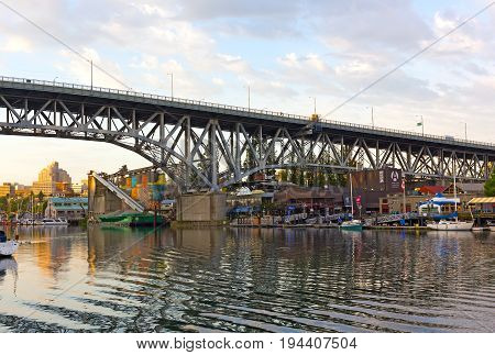 VANCOUVER CANADA - JUNE 26: Granville island with a famous public market and old industrial part along False Creek on June 26 2017 in Vancouver. Sunset over Granville Island with a view on the bridge and moored boats.