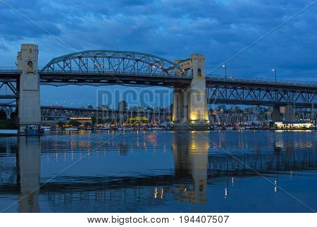 VANCOUVER, CANADA - JUNE 26: Burrard Bridge at dawn Granville Public Market with in a view on June 26 2017 in Vancouver Canada. Steel truss bridge over False Creek with imposing concrete towers before sunrise.