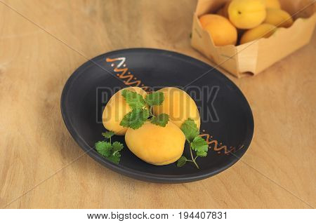 Delicious mature apricots on a brown ceramic plate, close-up.