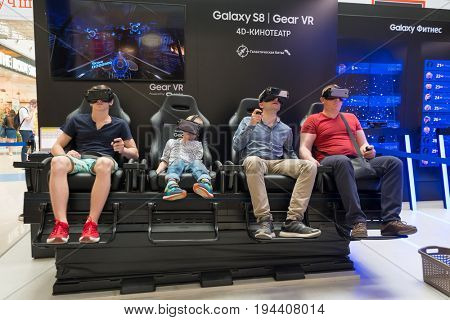 Moscow, Russia - June 11, 2017: People with an immersive VR content viewing experience at Samsung Gear VR Theater with 4D Chair in modern Interactive space Galaxy S8 Studio in Megapolis Shopping Mall.