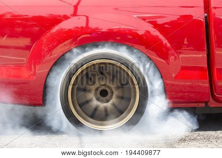 Drag racing car burns rubber off its tires in preparation for the race .