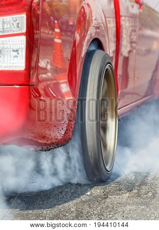 Drag racing car burns  tire in preparation for the race .