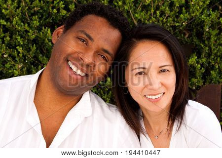 Portrait of a happy biracial couple sitting outside.