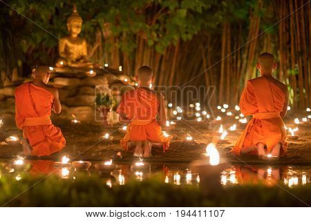 Asalha Puja Day ,Monks light candles and pray to buddha statue in Phan tao temple , Chiang mai ,Thailand .
