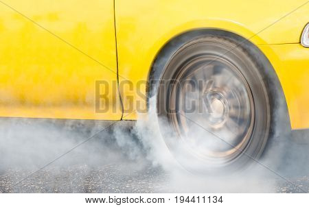 Drag racing car burns rubber off its tire in preparation for the race (front wheel drive) .