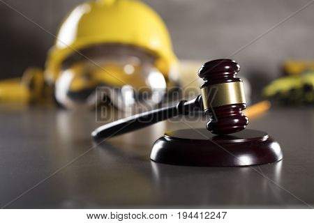 Construction law concept. Gavel and hardhat of the constructor.