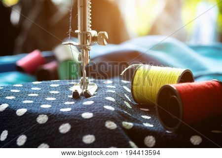 Sewing machine.sewing process in the phase of overstitching.Dressmaker work on the sewing machine.Tailor making a garment in workplace.Hobby sewing fabric as a small business concept poster