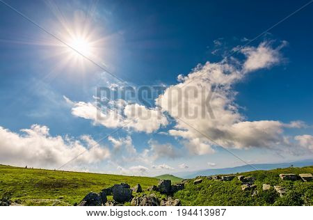 Sunburst On A Blue Sky With Clouds Over The Mountains