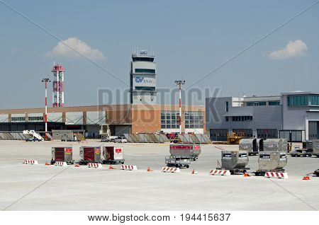 VENICE ITALY - JUNE 3 2017: Control tower and freight containers viewed on a sunny summer afternoon at Marco Polo Airport Venice Italy.