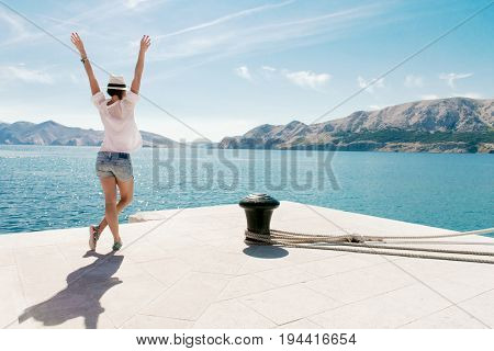 Happy woman on vacation standing by the sea. Arms raised. Carefree young female enjoy vacation. Beautiful young adult woman summer portrait.
