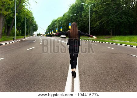 The girl is balancing on the dividing strip on the highway