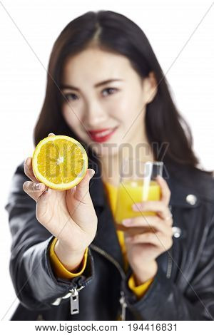 young asian woman hold a half of an orange and a glass of orange juice isolated on white background.