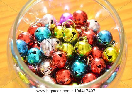 colorful bells in glass bottle on wooden board