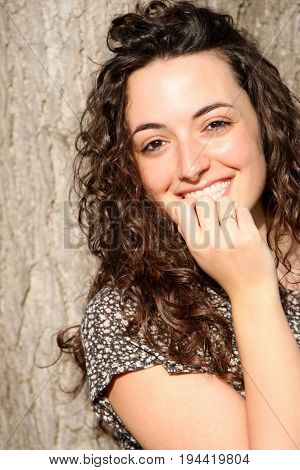 Beautiful and young smiling woman, long hair style. A young italian teenager stands near a tree and smiles. Long wavy hair. Hand over her mouth in shame.