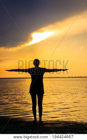 A young woman enjoys a warm evening on the shore of the estuary she spread her hands to the sides and admires the view