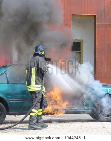 broken car with flames and black smoke and firefighter intervening to tamper with the fire poster