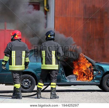 Incident Car With Flames And Black Smoke And Two Firefighters