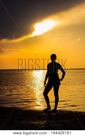 Silhouette of a young woman standing on the shore of the estuary she poses beautiful evening after her on the surface of the water formed a bright sunny path