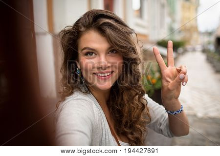 Young travel girl, having fun showing fingers on selfie photo. Woman walking in the street and making positive selfie shots.