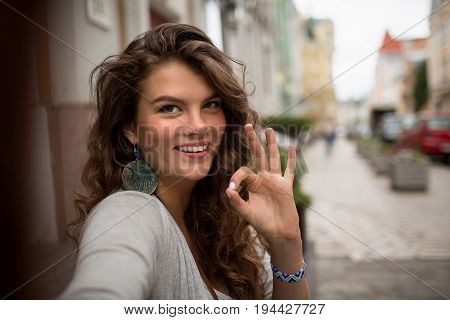 Woman walking in the street showing ok with fingers on selfie shot. Smiling girl with long curly hair and brown eyes.