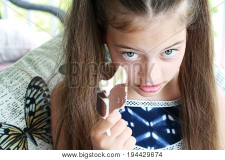 Young girl / child eating a messy dripping chocolate ice cream on a stick. Extreme shallow depth of field with selective focus on girls eyes and not ice cream.